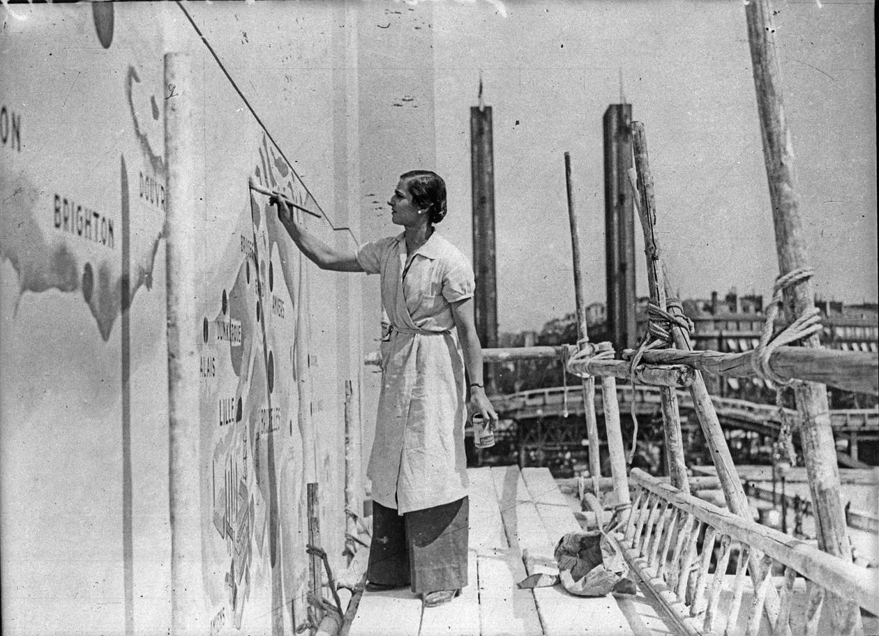Последний мазок краски на фасаде Павильона Туризма делает г-жа Пирр Гауди (2 июня 1937)