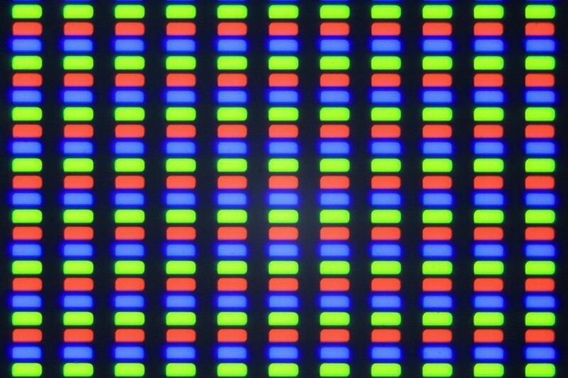 Фотография матрицы экрана телефона под микроскопом. Видны отдельные пиксели синего, зеленого и красного цветов