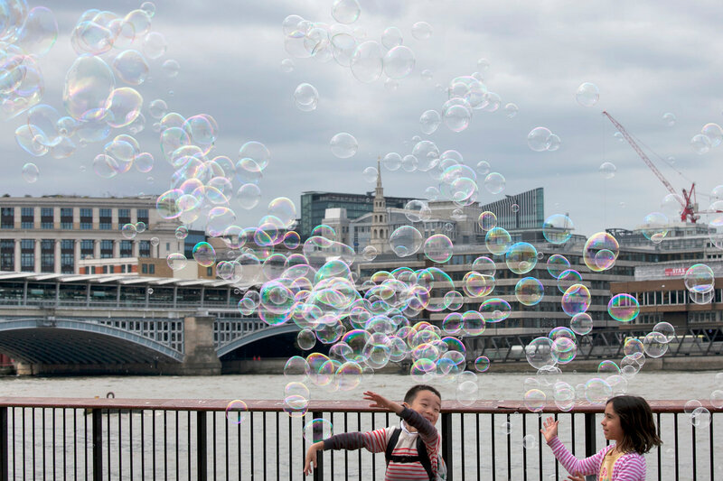 Children catch soap bubbles in the background of London