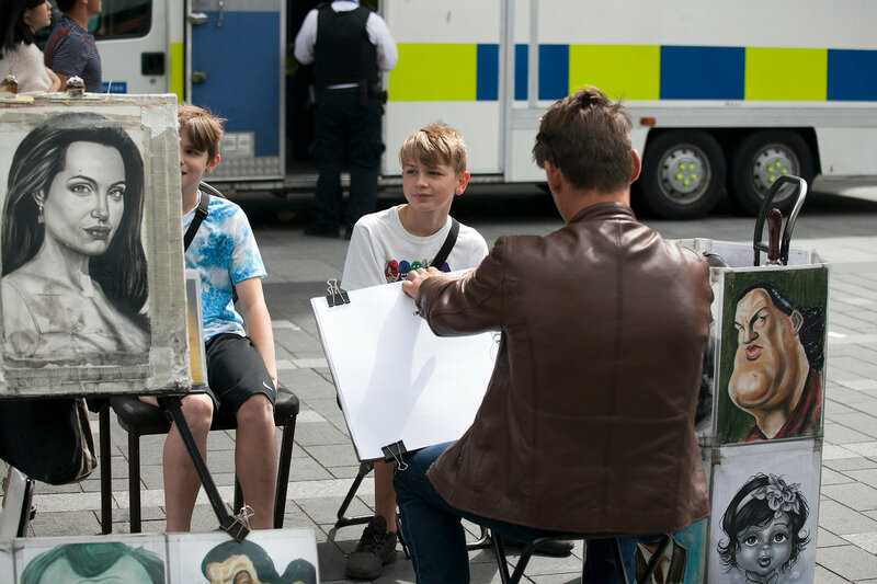 Street artist paints a portrait of a boy at Leicester Square