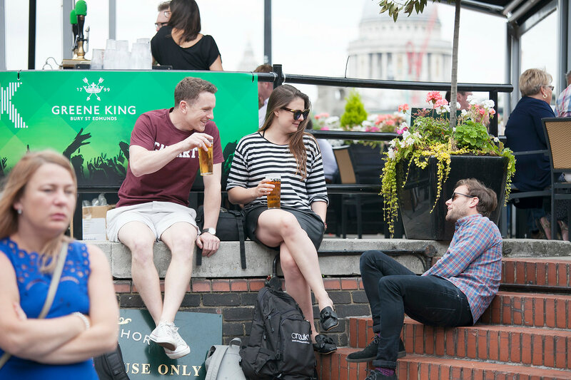 A motley crowd sits outside the pub, drinks beer, talks with friends. Southbank