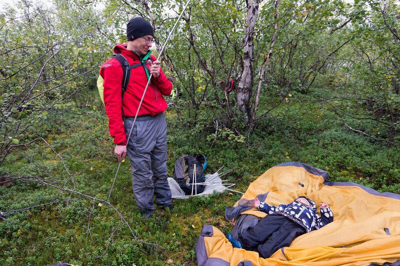 ребенок помогает ставить палатку в походе
