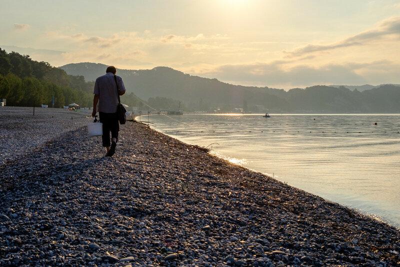 мужчина с ведром идет на рыбалку, черное море Абхазия, Лдзаа