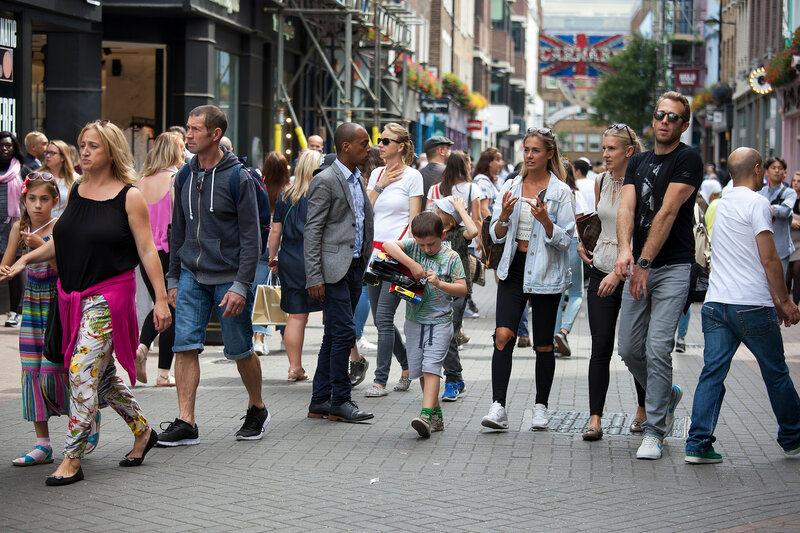 A multicolored crowd walks along Carnaby Street. Carnaby Street is one of the main shopping streets of London.