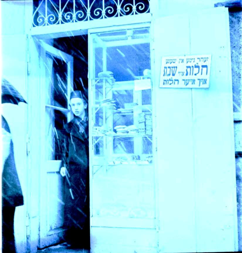 Мальчик стоит у входа в пекарню. Знак гласит «Очень хорошие и красивые халы на шабат« Казимеж