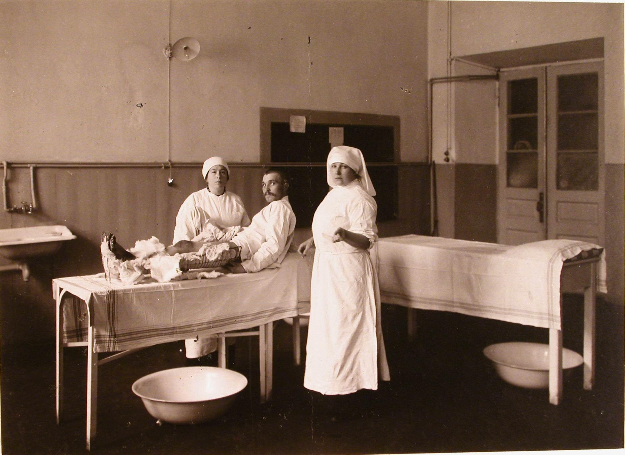 36. Сестры милосердия делают перевязку, раненому в перевязочной госпиталя №5