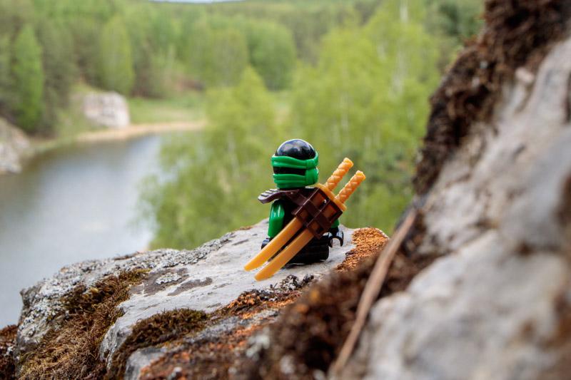 сидящий человечек Lego на скале возле реки в Разгуляевском парке