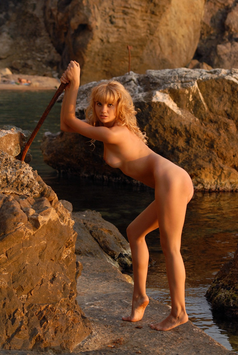Урсула позирует на прибрежных камнях