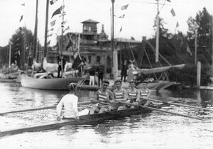 Команда спортсменов с тренером в гоночной лодке у лодочной станции перед началом состязаний.