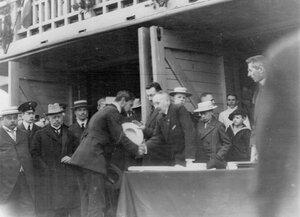 Председатель комиссии поздравляет члена гребного кружка с наградой; 1-й слева - А.Д.Макферсон