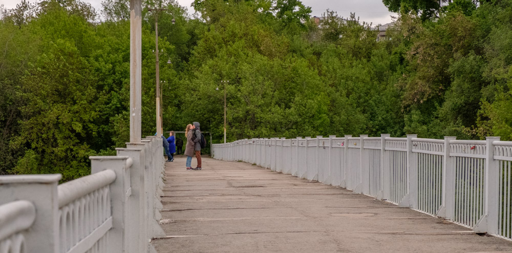 целующаяся пара стоящая на мосту