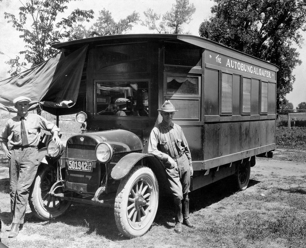"""H.B. Ley and T.S. Waud stand in front of the """"Autobungaloafer"""" camper at Overland Park auto camp in the Overland neighborhood of Denver, Colorado. 1921."""