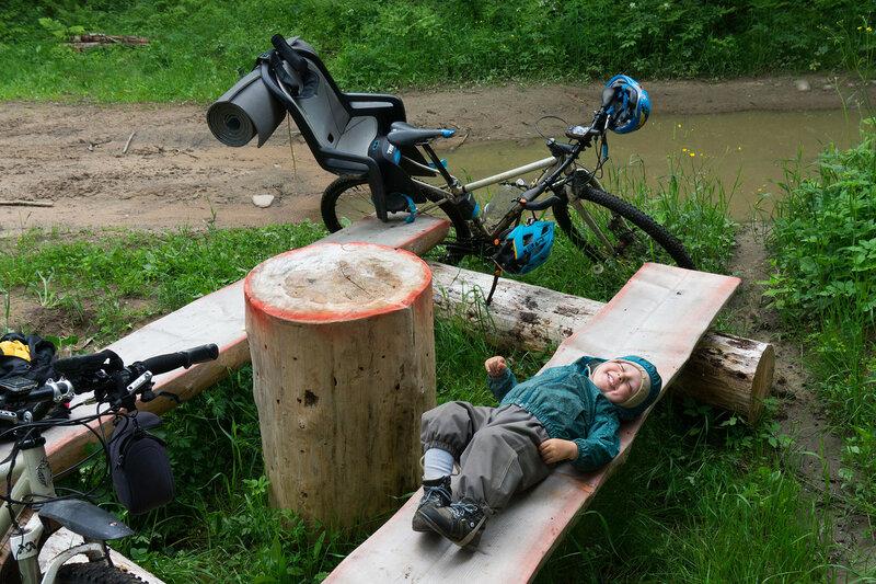 радостный ребенок отдыхает на скамейке в велопоходе по карельскому