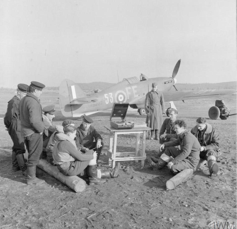 Персонал RAF и советские моряки стоят вокруг патефона на аэродроме