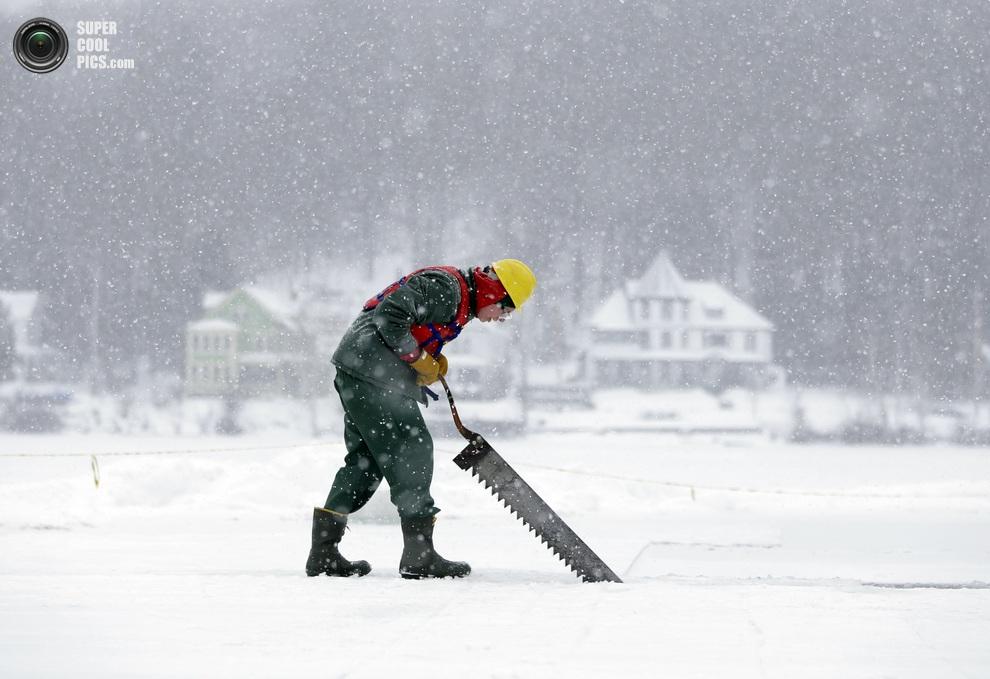 Адам Блосс (Adam Bloss) из Рочестера нарезает блоки льда на озере Флауэр. (AP Photo/Mike Groll)