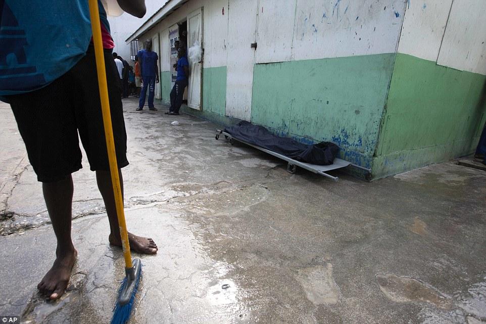 Один из заключенных стоит рядом с телом умершего от истощения сокамерника.