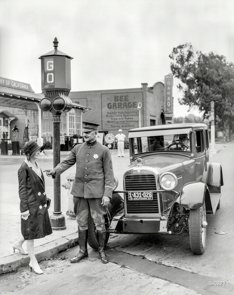 San Francisco, 1927. Traffic signals -- police officer stops pedestrian crossing against the light in front of Hudson sedan at Bee Garage service station