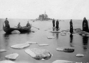 Схимник и послушники на прибрежных камнях острова Коневец.