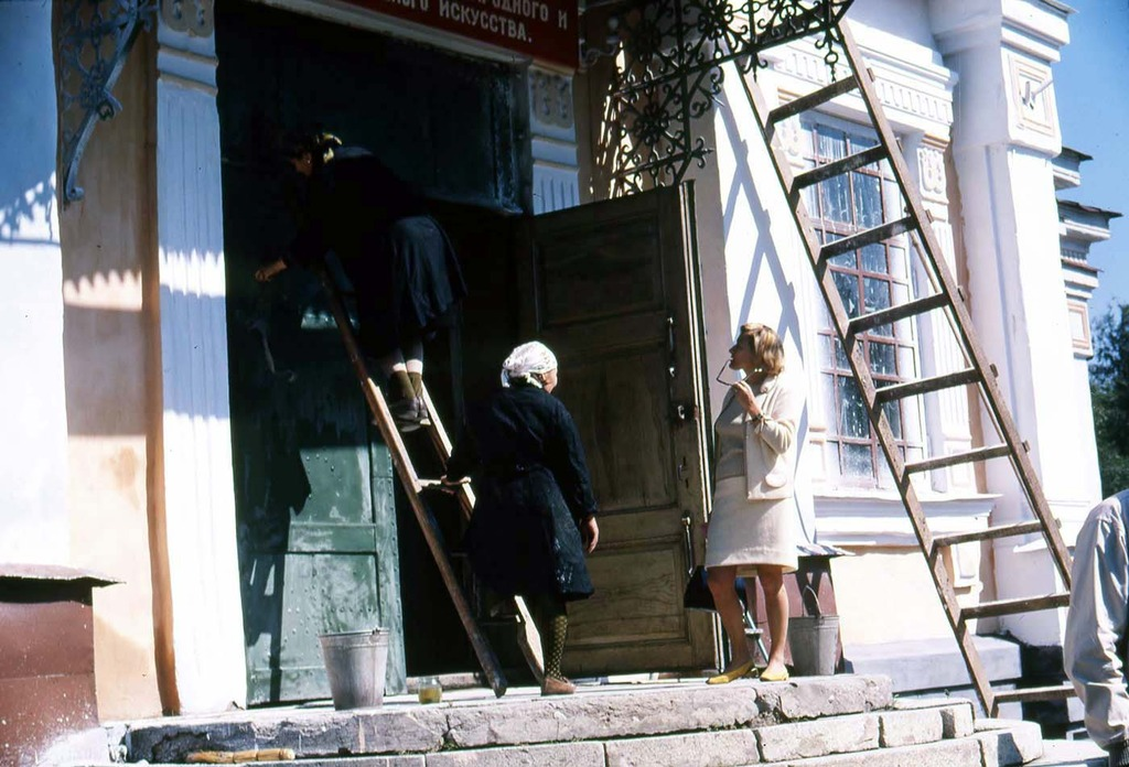 two women cleaning the front entrance of a church while talking to Phyliss Snider.JPG