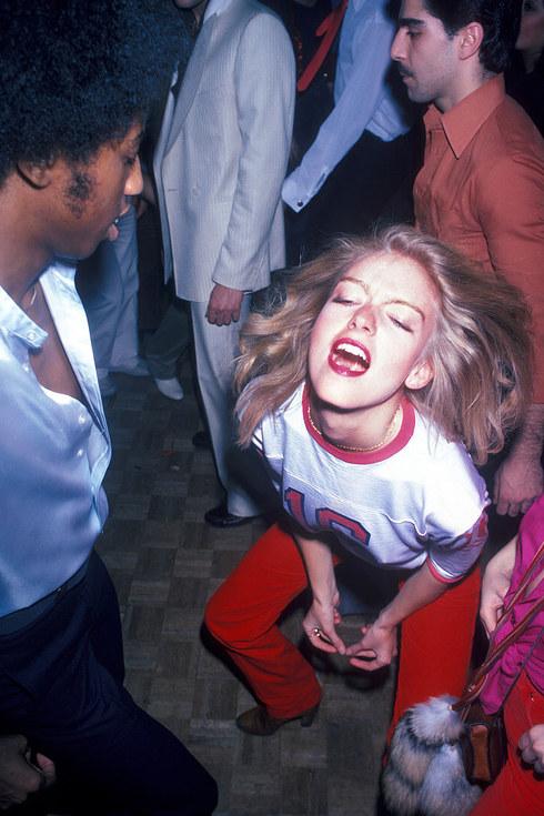 Девушка танцует в толпе на танцполе Studio 54, 1977 год.