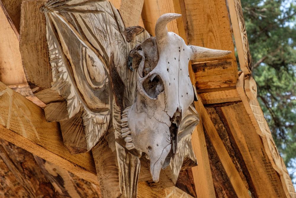 череп коровы висящий на входе в деревянное здание