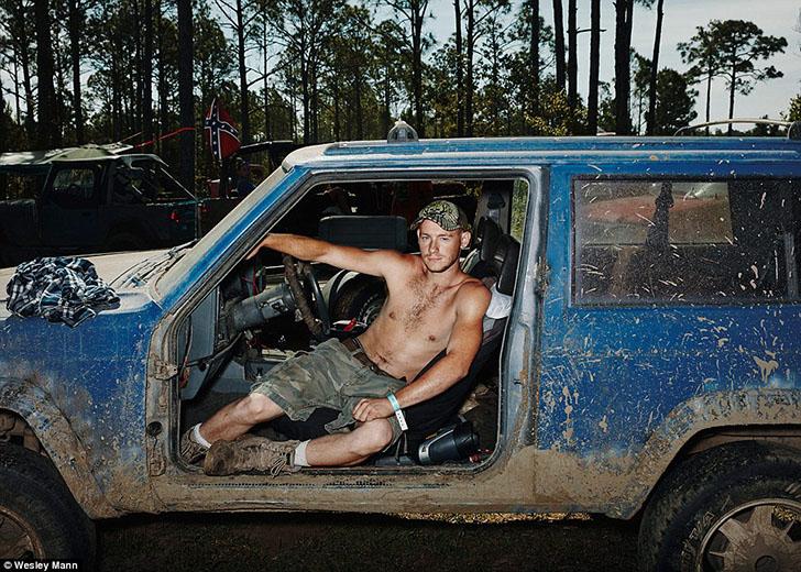 Мужчина позирует в своем внедорожнике, где полностью отсутствуют боковые двери, из-за чего грязь лег