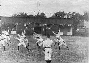 Группа членов Гимнастического общества Пальма делает вольные упражнения на спортивной площадке