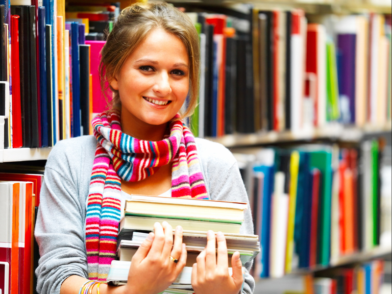 Pretty charming lady holding books in library