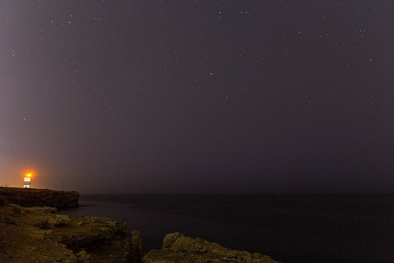 Маяк на скалистом берегу Чёрного моря ночью среди звёзд (Севастополь, Крым)