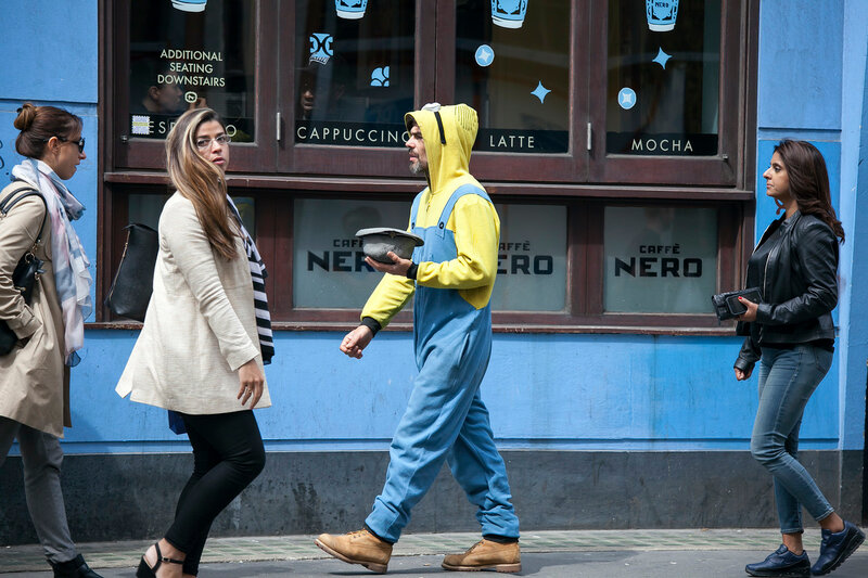 Passers-by walking along the street. A beggar man in a yellow suit and a hat in his hand asks for money