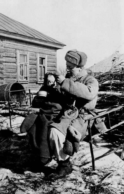 Советский автоматчик кормит ребенка.