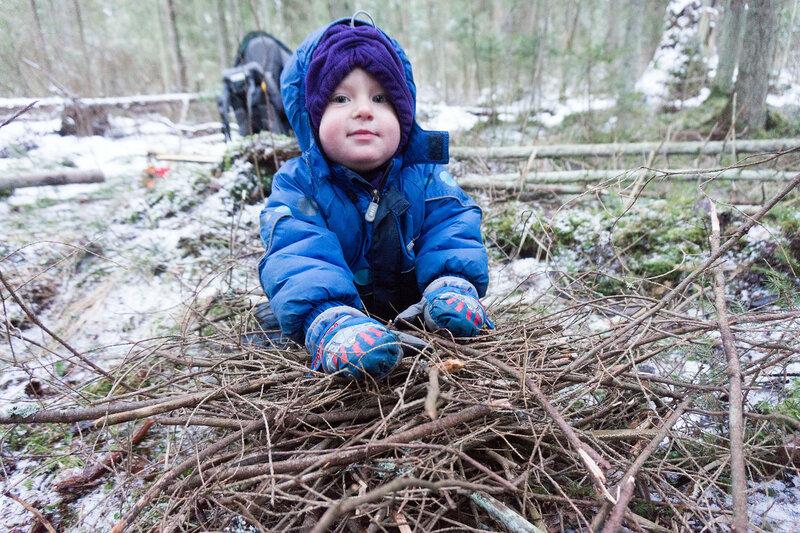 ребенок складывает палки в костер в пешем походе в лесу