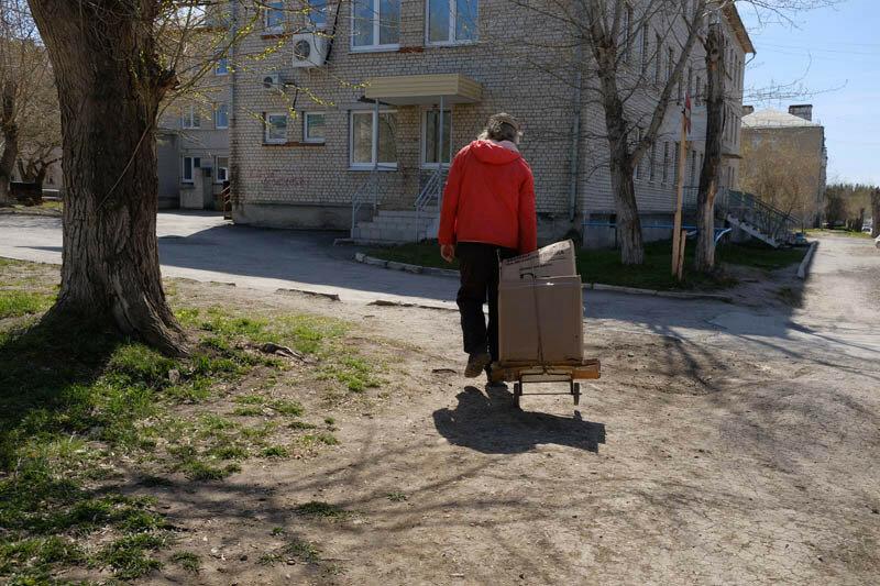 мужчина тащит за собой тележку с картоном