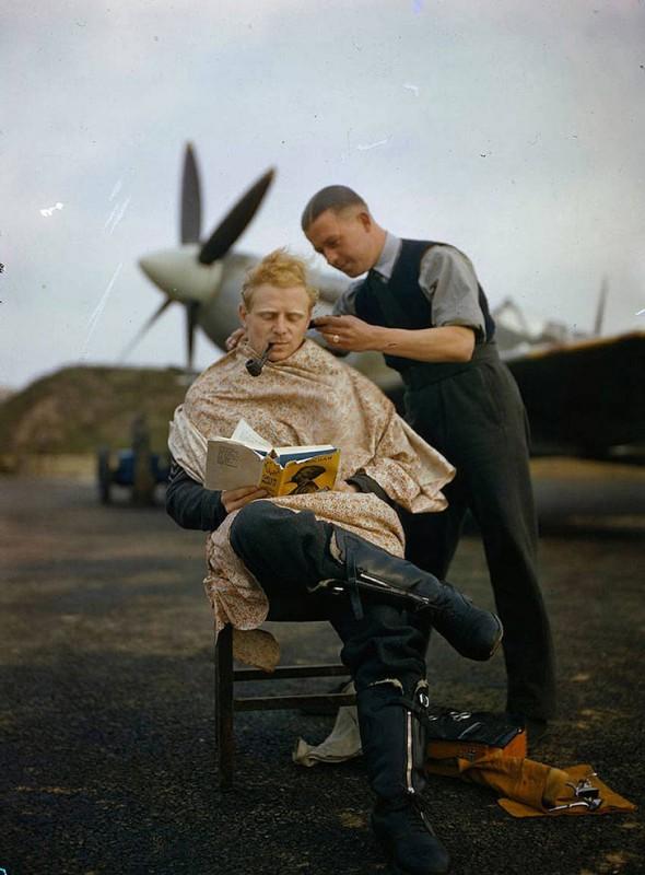 Парикмахер стрижет пилота РАФ в перерыве между полетами.