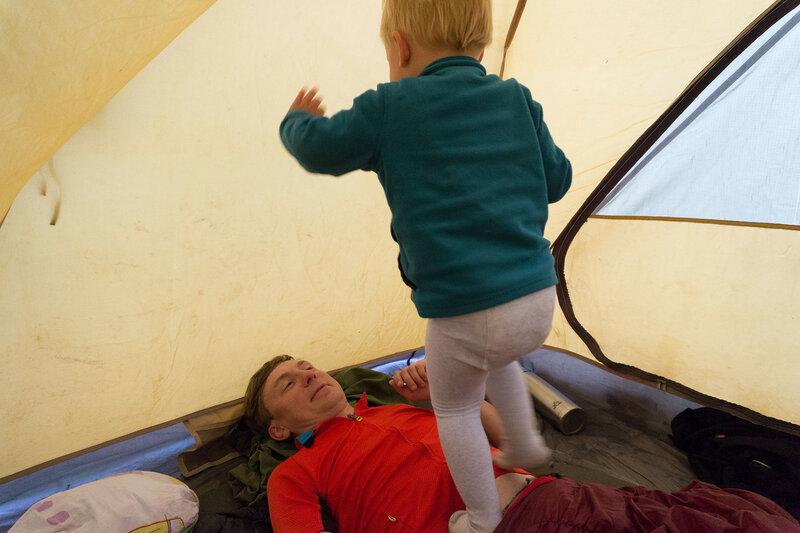ребенок прыгает на папе в палатке