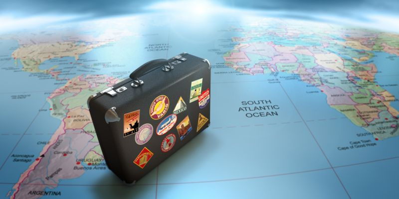 Открытка. День туризма. Чемодан на карте мира