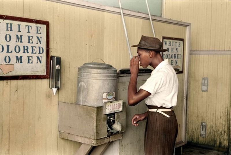 Афроамериканец пьет воду. Надпись на автомате: «Для цветных». Оклахома, июль 1939 года.