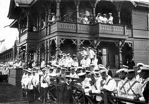 Зрители на трибунах ипподрома, наблюдающие за происходящими скачками; на балконе трибун император Николай II и члены императорской фамилии