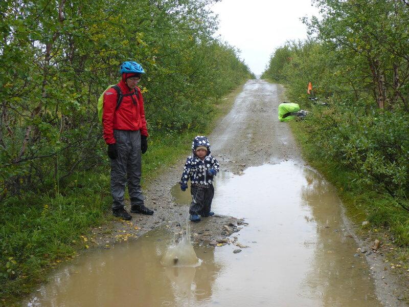 ребенок кидает камни в лужу в походе под дождем