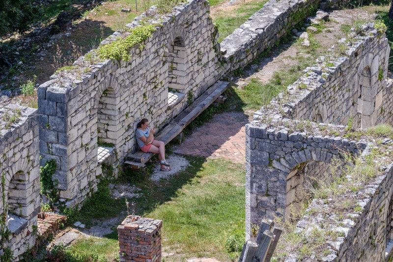 уставший турист на вершине Иверской горы скрывается от солнца за стеной крепости