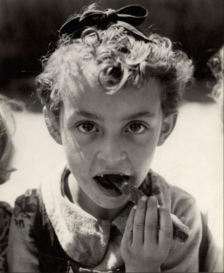 Голодный ребенок грызет корку хлеба в летнем лагере ОЗЗ (Общество по охране здоровья еврейского населения) в Отвоке