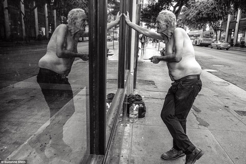 По пояс голый мужчина стоит у витрины магазина с ножом в руке, глядя на свое отражение.