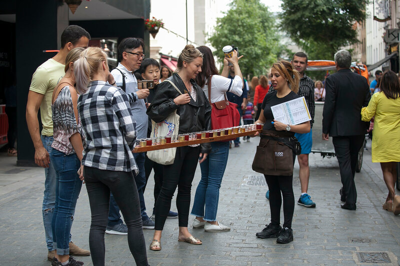 Girls promouters keep glasses of beer on a long tray. Girls are advertising a beer restaurant near Covent Garden.