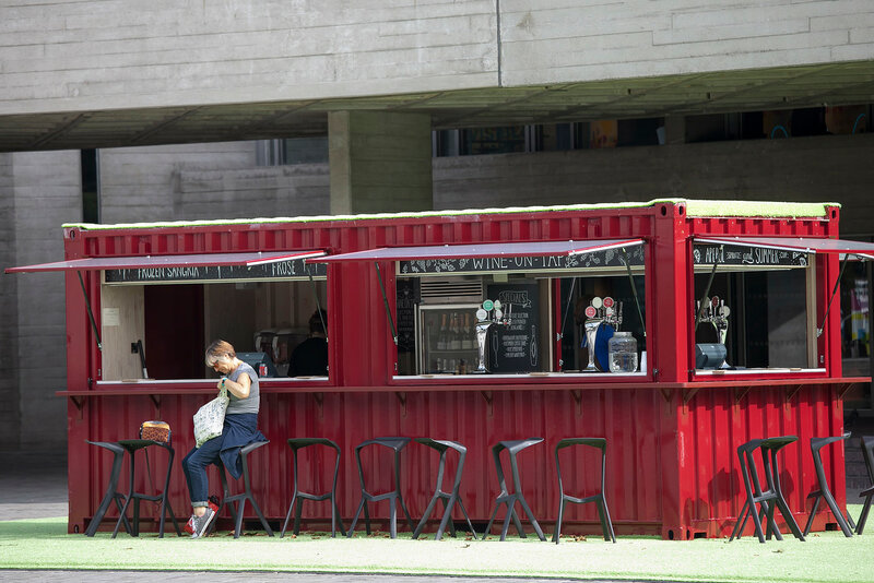 Red wagon converted into a street cafe near the National Theater. A woman is waiting for her coffee, sitting on a high stool.
