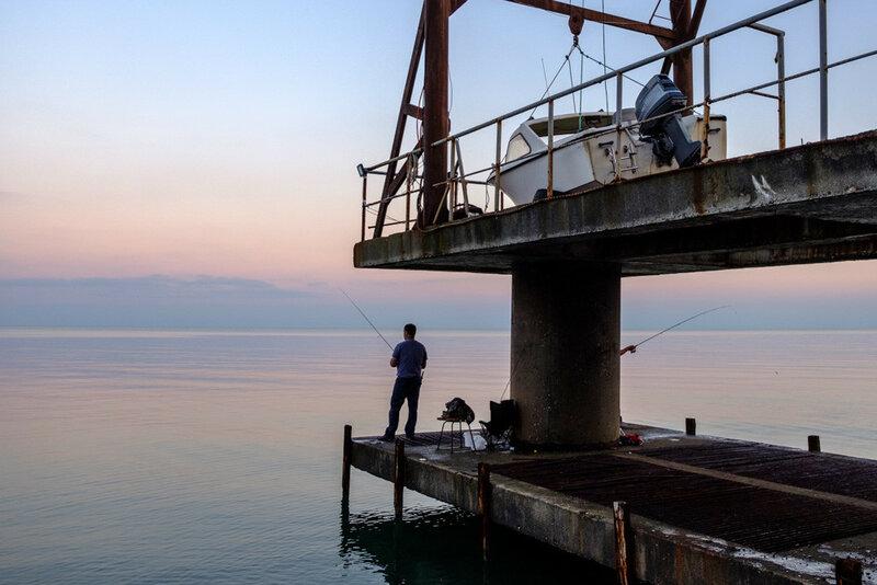 рыбаки на пирсе Черное море, Абхазия