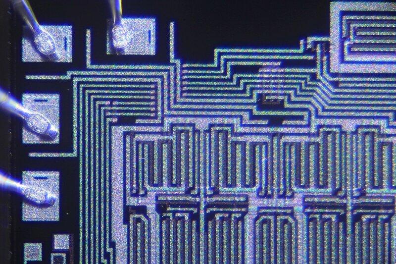 Фотография микросхемы под микроскопом. Видны дорожки элементов логики на кремниевой подложке и металлические крепления контактов к пластине
