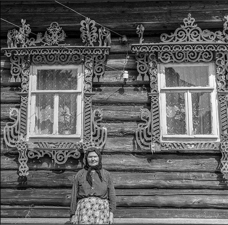 Хозяйка дома на фоне фасада с резными окнами