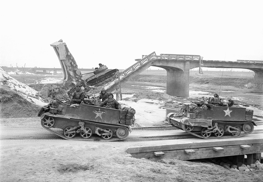 British gun carriers, heading south, pass a knocked-out Russian T-34 tank on a demolished bridge at