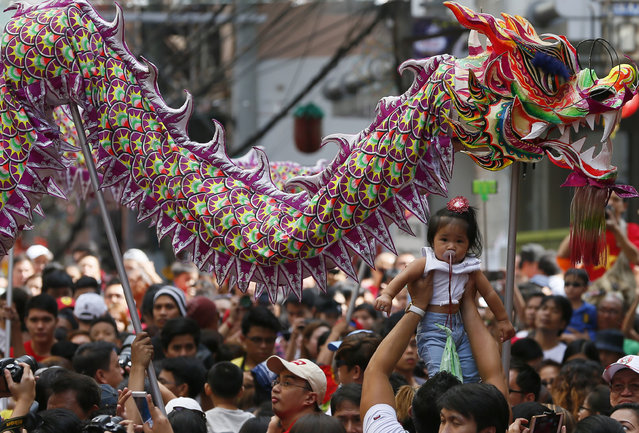 A reveler raises a baby as dragon dancers make their through a crowd to perform in celebration of th
