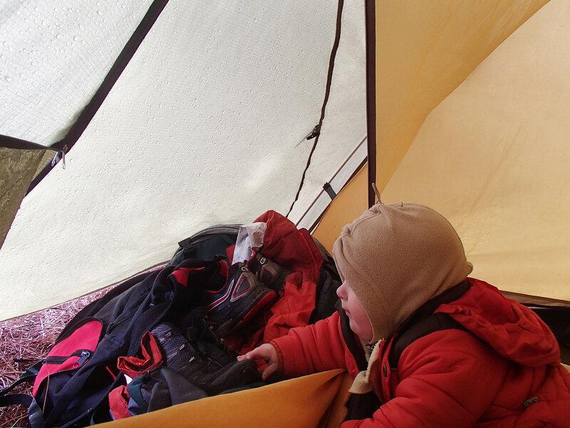 ребенок смотрит на снег из палатки
